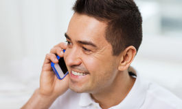 Happy man calling on smartphone at home Royalty Free Stock Photography