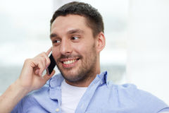Happy man calling on smartphone at home Stock Photo