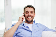 Happy man calling on smartphone at home Royalty Free Stock Images