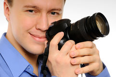 The happy man with the camera. The happy man holds the camera in hands Royalty Free Stock Photo