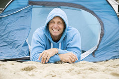 Happy man camping. A colour portrait photo of a happy smiling forties man laying in his tent on the beach during a vacation Royalty Free Stock Photo