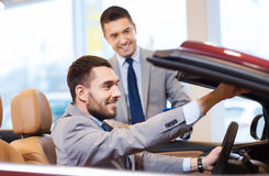 Happy man with car dealer in auto show or salon Stock Image