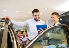 Happy man with car dealer in auto show or salon Royalty Free Stock Image
