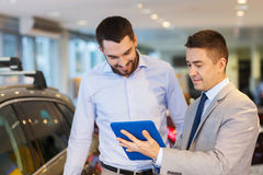 Happy man with car dealer in auto show or salon. Auto business, car sale, technology and people concept - happy men and car dealer with tablet pc computer in Stock Photography