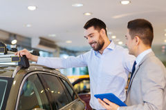 Happy man with car dealer in auto show or salon Royalty Free Stock Photography