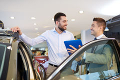 Happy man with car dealer in auto show or salon Stock Images