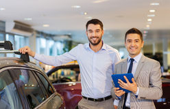 Happy man with car dealer in auto show or salon Royalty Free Stock Photos