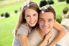 Happy man carrying on back wife in garden Royalty Free Stock Photos