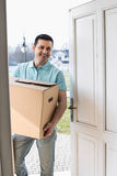 Happy man carrying cardboard box while entering new house Royalty Free Stock Photos
