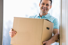 Happy man carrying cardboard box at entrance of new house Royalty Free Stock Image