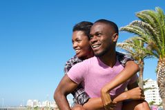 Happy man carrying girlfriend outdoors. Close up portrait of a happy men carrying girlfriend outdoors stock images