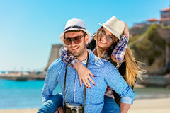 Happy man carrying his girlfriend on a piggyback ride both smiling and looking very happy enjoying their vacation. Happy men carrying his girlfriend on a royalty free stock images