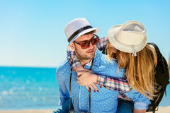 Happy man carrying his girlfriend on a piggyback ride both smiling and looking very happy enjoying their vacation. Happy men carrying his girlfriend on a stock photos