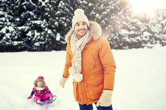 Happy man carrying little kid on sled in winter. Childhood, sledding, leisure, season and people concept - happy men or father carrying little kid on sled in Royalty Free Stock Photos