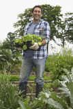 Happy Man Carrying Plants In Field Royalty Free Stock Photos
