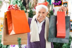 Happy Man Carrying Shopping Bags In Christmas Royalty Free Stock Photography