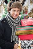 Happy Man Carrying Stacked Gift Boxes Stock Photo