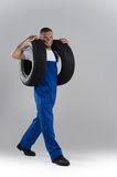 Happy man carrying tire on grey background. Stock Images