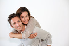 Happy man carrying wife on back Stock Images
