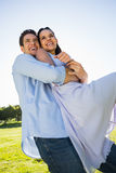 Happy man carrying woman at the park Royalty Free Stock Photography