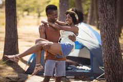 Happy man carrying woman while standing against tent Stock Photography