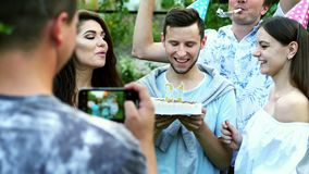 Happy man celebrates a birthday, blows out candles on a cake, friends congratulate, take a photo on mobile phone stock video