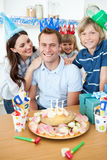 Happy man celebrating his birthday with his family. In the kitchen Stock Photo