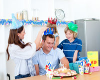 Happy man celebrating his birthday with his family. Delighted man celebrating his birthday with his family in the kitchen Royalty Free Stock Photos