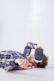 Happy man in checkered shirt. Lies on floor in white room and play in virtual game Stock Image