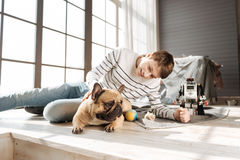 Happy man-child staring on his dog Stock Photos