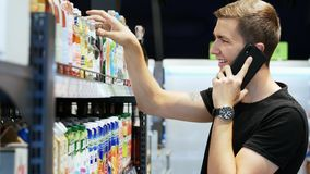 Happy man chooses products in the Supermarket and talking on a mobile phone, customer selects goods on the shelves in stock footage
