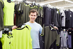 Happy man chooses sport t-shirt in shop Royalty Free Stock Photography