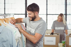 Happy man choosing clothes for donation Royalty Free Stock Image
