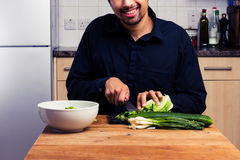 Happy man chopping vegetables Stock Photos