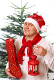 Happy man in Christmas cap is holding big red sack Royalty Free Stock Image