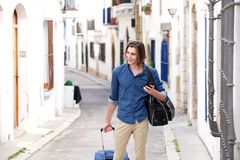 Happy man in city street with smart phone and luggage Royalty Free Stock Image