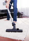 Happy man is cleaning in the modern room with vacuum. Royalty Free Stock Photos