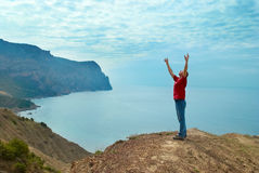 Happy man on the cliff. Happy man standing on the cliff with hands up looking at the sea royalty free stock images