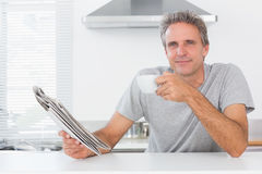Happy man with coffee and newspaper stock photos