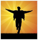The happy man 2. Composition with the image of a man`s silhouette. The man runs on a grass. On a distance shot the sun shines Stock Photos