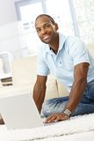 Happy man with computer. Portrait of happy handsome afro man using laptop computer at home on the floor royalty free stock image