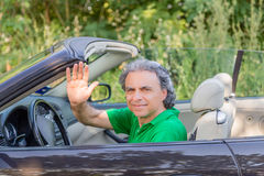 Happy man on convertible car. Mature man driving a convertible car  is happy and shows his satisfaction by smiling and raising his hand to greet Stock Photo