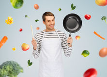 Happy man or cook in apron with pan and spoon Royalty Free Stock Photos