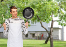 Happy man or cook in apron with pan and spoon Stock Photography
