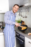 Happy man cooking egg omelet in the kitchen Royalty Free Stock Images