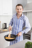 Happy man cooking egg omelet in the kitchen Royalty Free Stock Photography