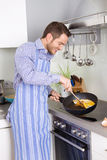 Happy man cooking egg omelet in the kitchen. Royalty Free Stock Images