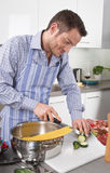 Happy man cooking pasta in the kitchen Stock Images