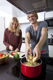 Happy man cooking pasta with woman in kitchen Stock Photos