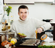 Happy man cooking raw fish with lemon in roasting pan Royalty Free Stock Image